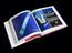"""Book entitled """"Cancer Vixen - a True Story"""". Top three quarter view of open book. Black background."""
