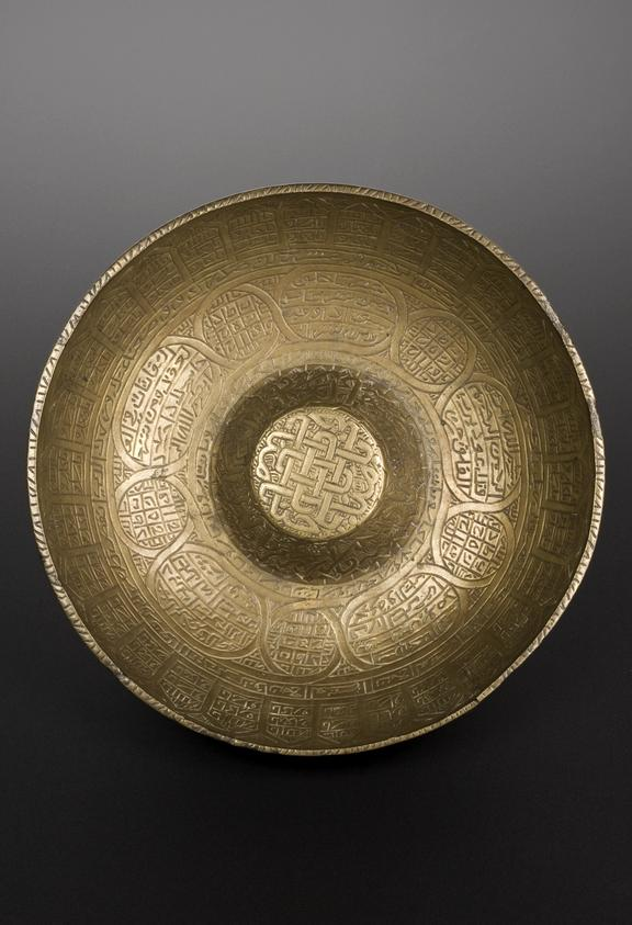 Engraved brass divination bowl, Persian or Palestinian, 19th century. Top view, graduated matt black perspex background.