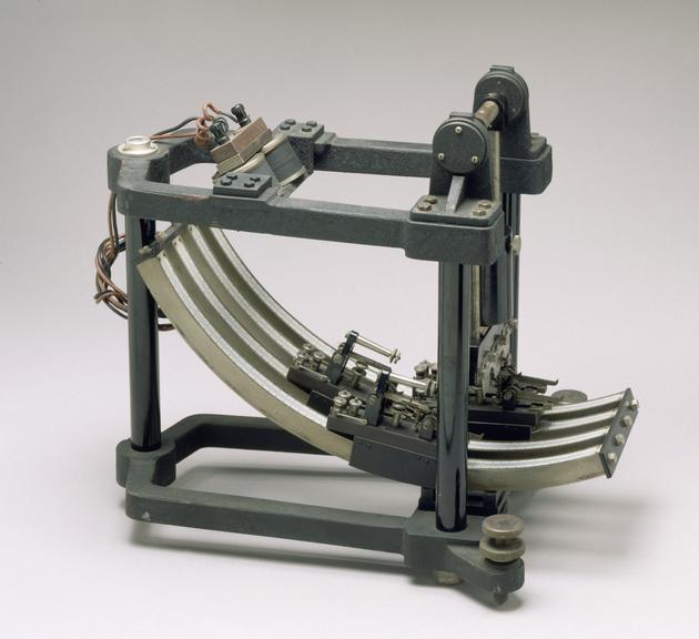 Helmholtz pendulum, German, c1900. Front three quarter view. Graduated grey background.