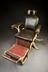 Dental chair with hydraulic adjustment, c.1900. Full 3/4 view, graduated grey background.