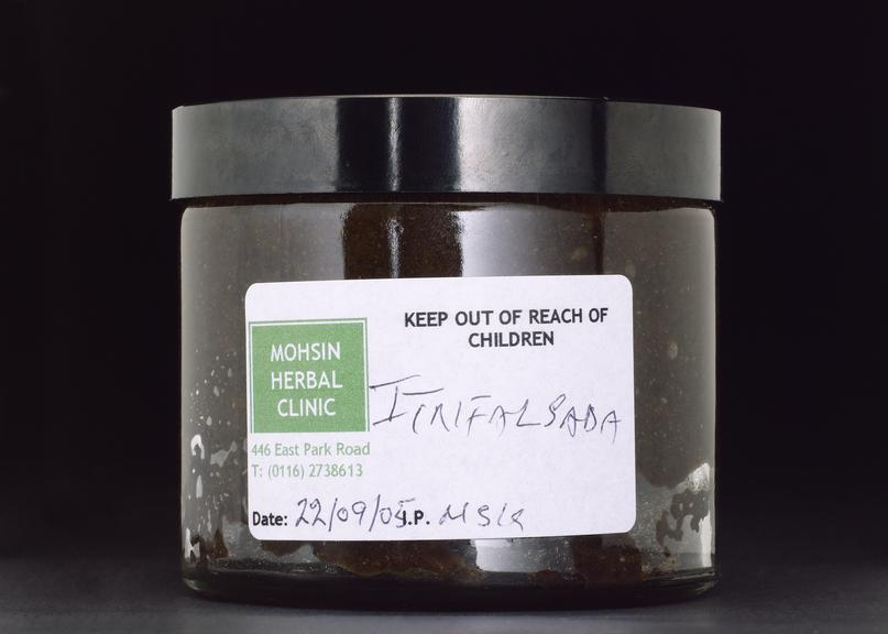 Moshin Herbal Clinic's Trifola paste. Front view. Black background.