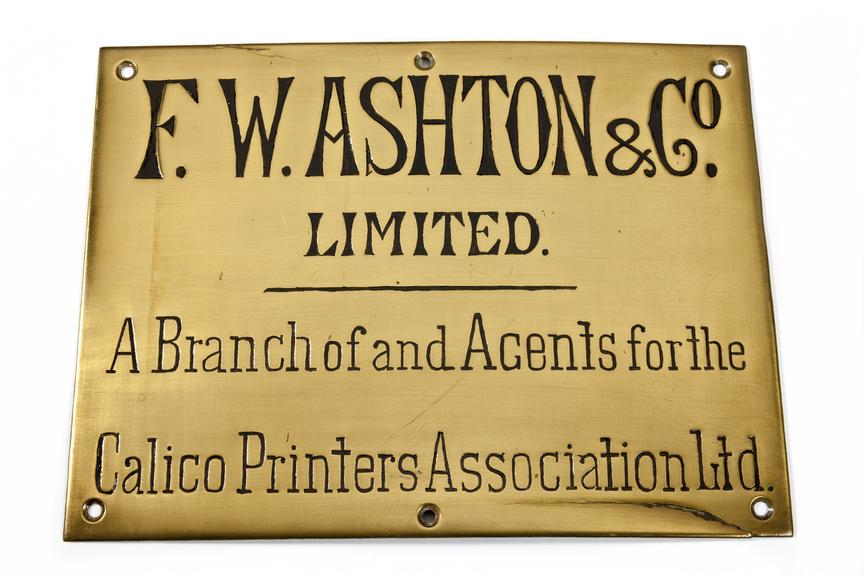 Brass sign, F.W Ashton & Co..Photographed from above on a white background.