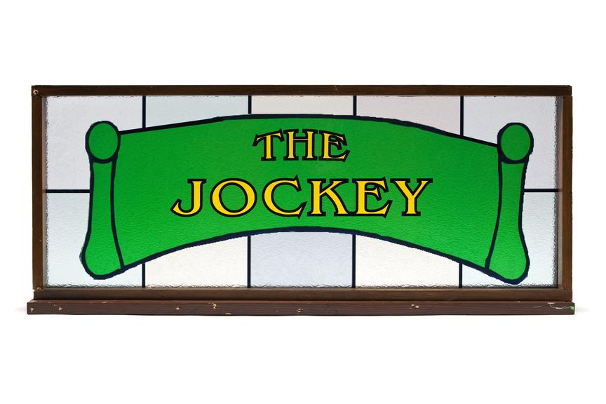 Glass pub sign 'The Jockey' used in the making of shameless tv series..Straight on view on a white background.