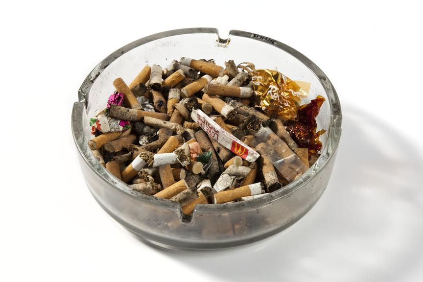 Full ashtray used in the making of shameless tv series..Three quarter view on white background..