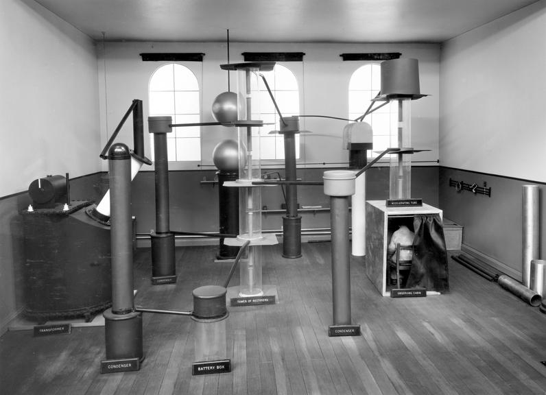 """Model of Cockcroft and Walton's """"atom-splitting"""" Research Laboratory at Cambridge, scale approx 1:8. From a black &"""
