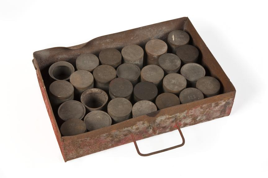Set of miner's wage tins in a drawer..Photographed 3/4 view on a white background.