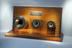 Presentation display of Presentation display of three gold-plated cable dies on wooden stand on the on wooden stand on