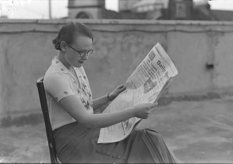 Woman reading the Daily Herald newspaper       A photograph of a young woman reading the Daily Herald newspaper