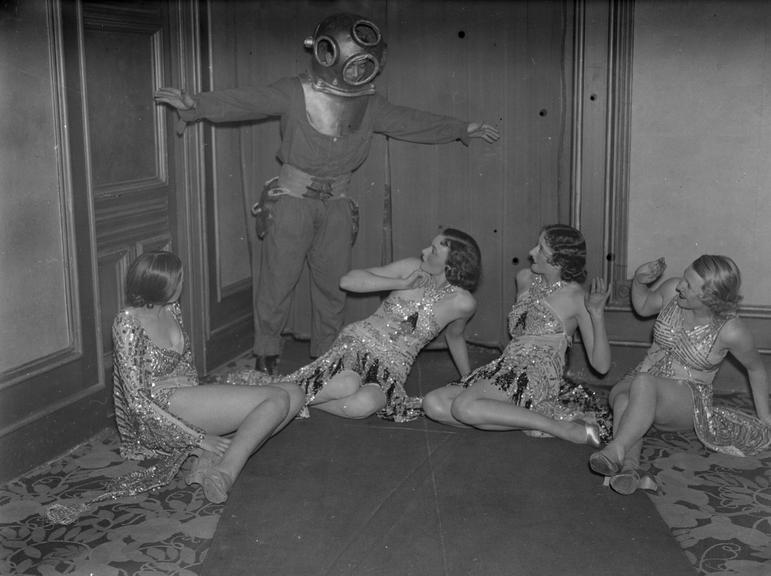 'Some of the Jackson Girls'       A photograph of members of the Jackson Girls dance troupe being surprised by a man wearing a diving suit