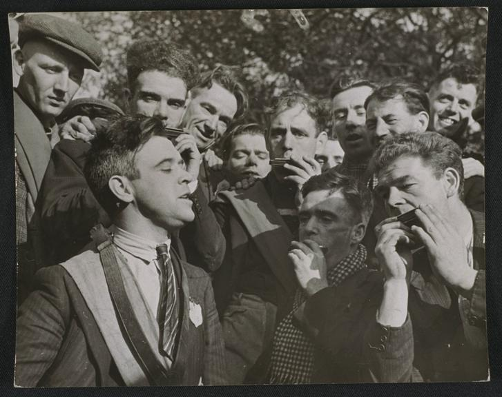 ''Croonin' J McCauley sings to some of his fellow Jarrow marchers'        A photograph of J McCauley, a Jarrow marcher singing to his co-marchers on their walk to London, taken by E.G