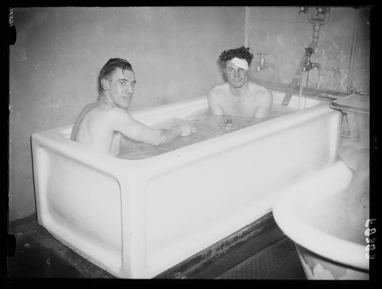 Two footballers share a bath       A photograph of two footballers bathing together after a match