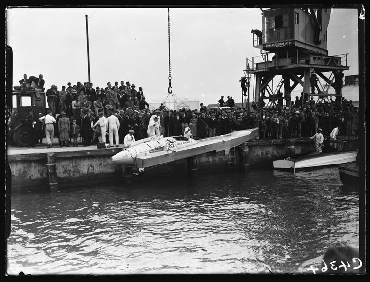 'Miss Britain III' speedboat       A photograph of crowds gathered to see the 'Miss Britain III' speedboat being lowered into the sea at Poole, Dorset
