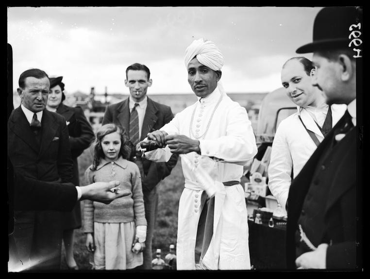 'A tipster performing tricks at Epsom'       A photograph of Abdul Gaffoor performing conjuring tricks at Epsom on Derby Day