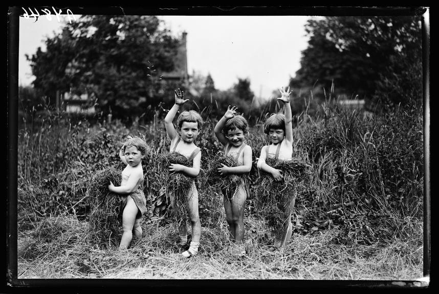 Four children in a field       A photograph of four little children playing with cut grass in a field and waving for the camera