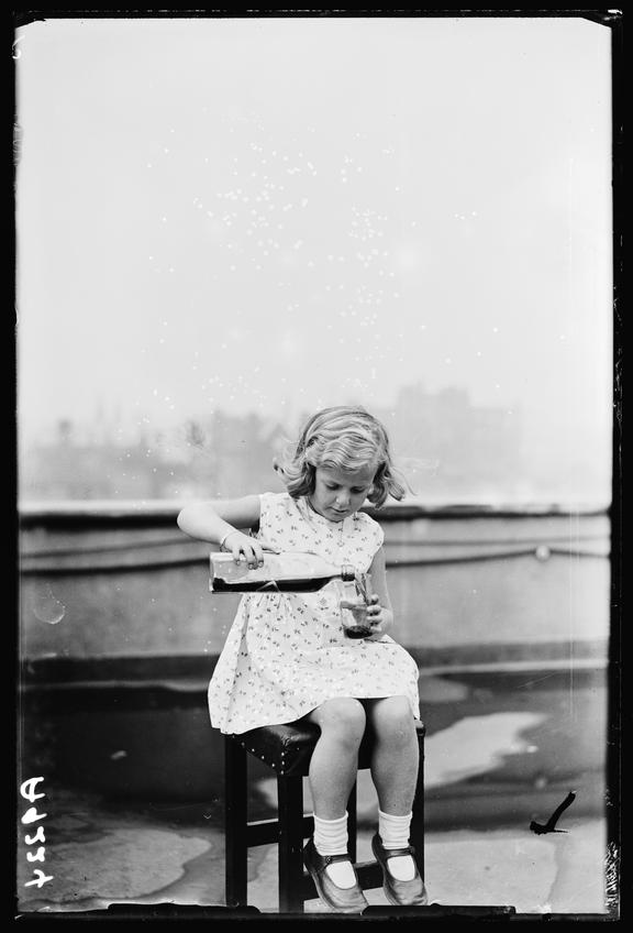 Little girl pouring whisky       A photograph of a little girl sitting on a stool pouring herself a glass of whisky