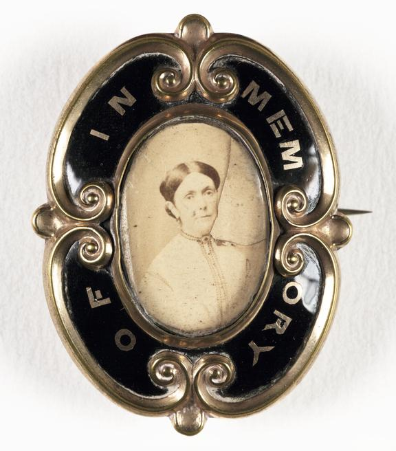 Photographic memorial brooch       A photographic portrait of a woman set into a memorial brooch, taken by an unknown photographer in about 1880