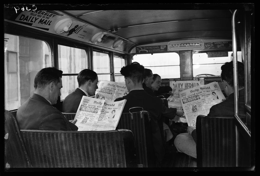Bus passengers reading the Daily Herald newspaper       A photograph of passengers on a London General Omnibus reading the front page of the Daily Herald