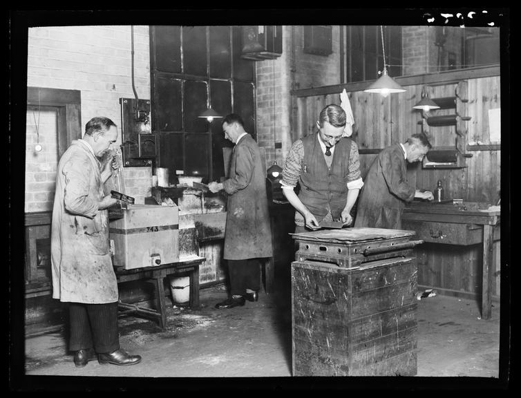 The process department       A photograph of men in overalls working in the Daily Herald process department
