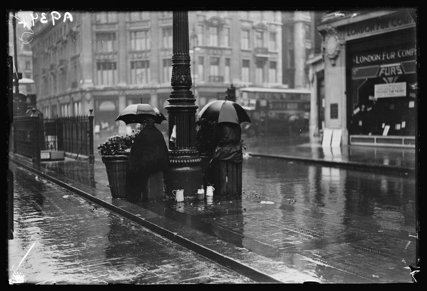 London flower sellers       A photograph of flower sellers huddled beneath umbrellas on a wet London street
