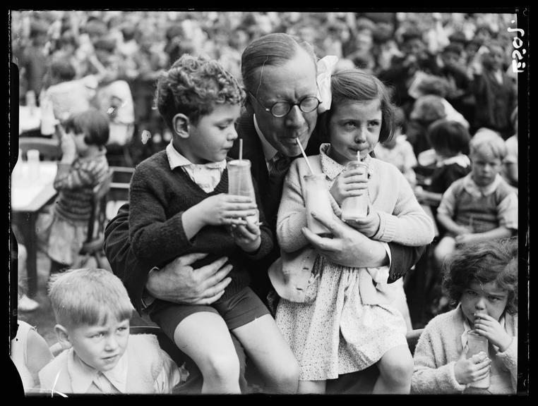 Drinking milk       A photograph of Major Elliot, Minister of Agriculture, lifting up two children in his arms