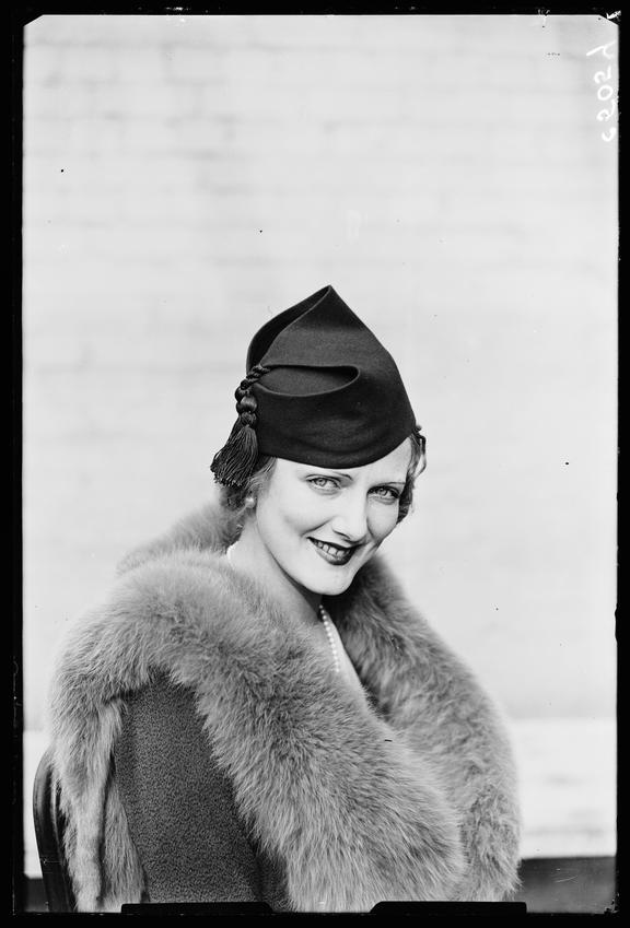'Woman displaying latest hat fashion'       A photograph of a model wearing the latest fashion in women's hats
