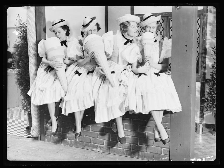 Women eating giant ice cream cones       A photograph of four women in milkmaid costumes pretending to eat giant ice cream cones