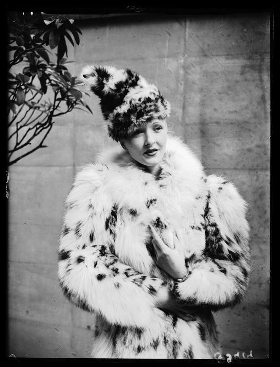 Woman wearing a fur coat       A photograph of a woman wearing a snow leopard fur hat and coat ensemble