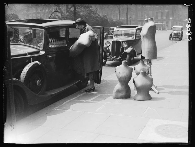Unloading dressmaking dummies from a car       A photograph of a woman unloading dressmaking dummies from a parked car