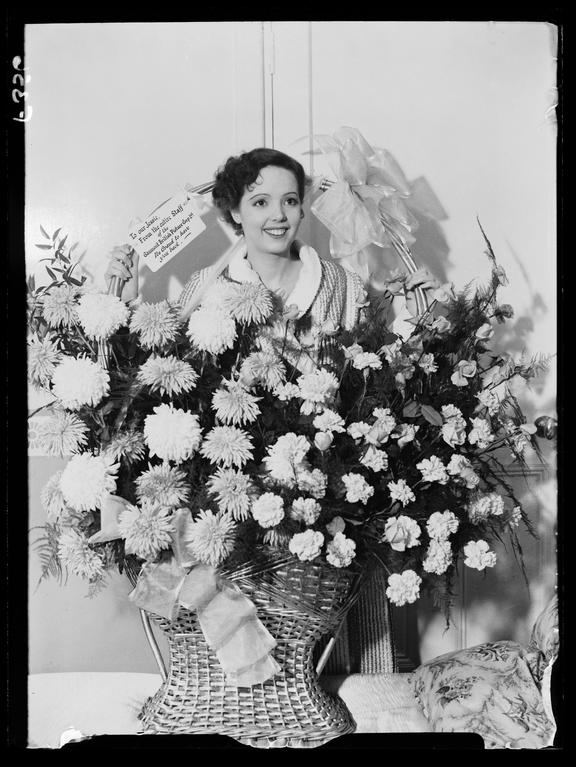 'Jessie Matthews with a floral gift'       A photograph of Jessie Matthews (1907-1981) standing within a flower arrangement she has just received
