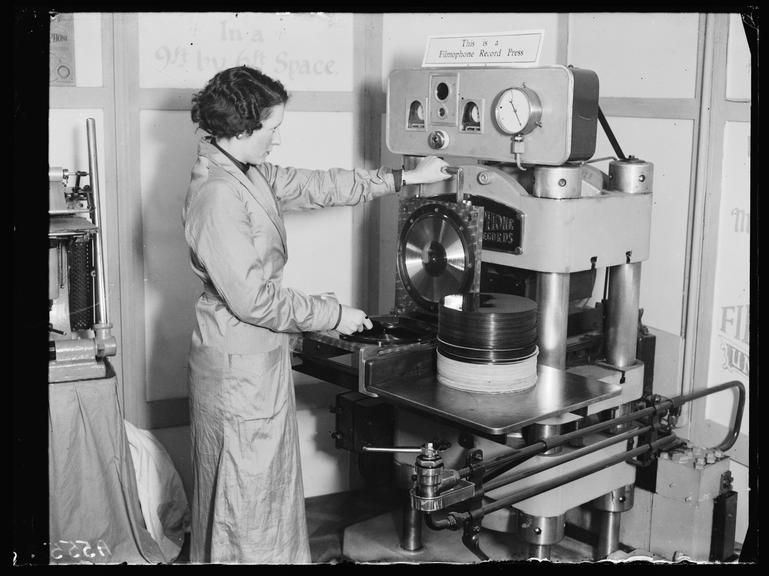 'Pressing a record'       A photograph of a woman pressing phonograph records on a 'Filmophone' machine