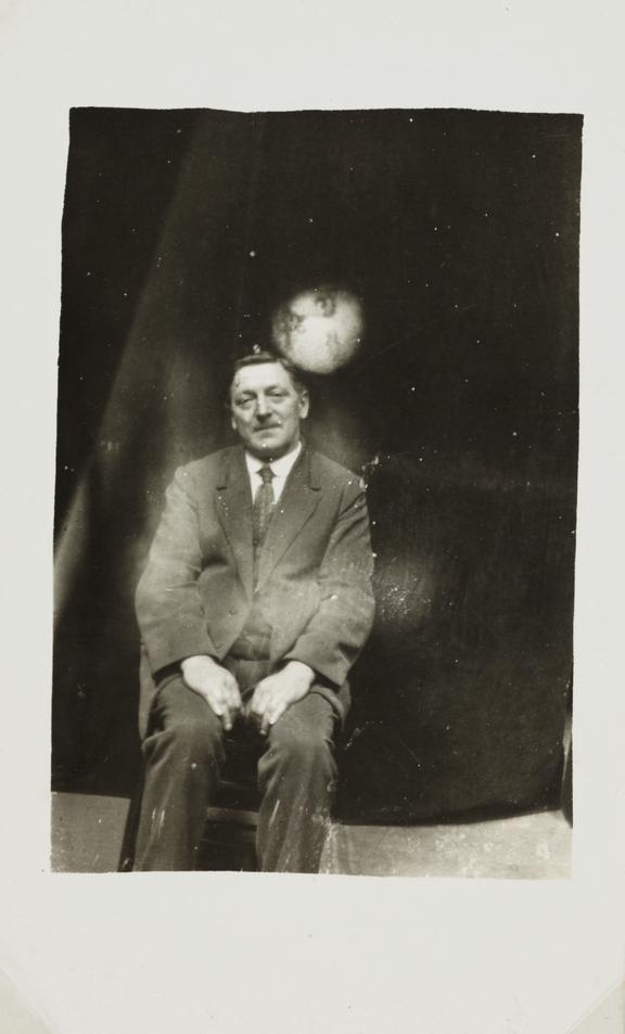 Man with 'spirit face' appearing       A photograph of a man, taken by William Hope (1863-1933) in about 1920