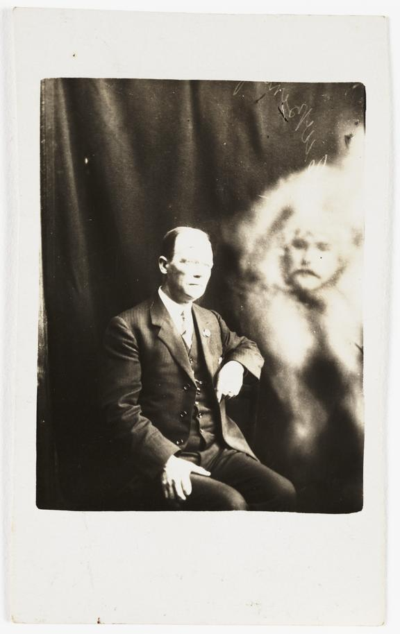 Man with 'spirit face' appearing       A photograph of a man, possibly taken by William Hope (1863-1933) in about 1920