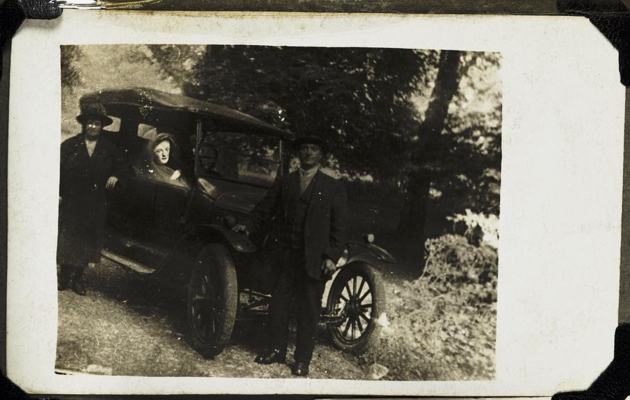 Couple with a 'spirit' in their car       A photograph of a couple leaning against a car, taken by William Hope (1863-1933) in about 1920