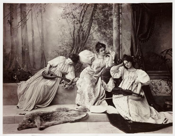 Three women with musical instruments       A posed tableau studio photograph of three young women, two of whom are holding musical instruments