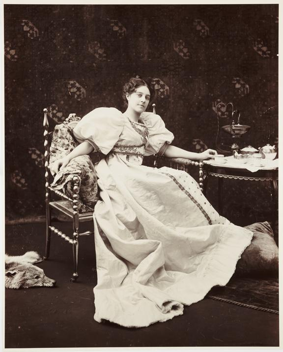 Seated woman drinking tea       A studio photograph of young woman drinking a cup of tea, taken by James Arthur in about 1900.