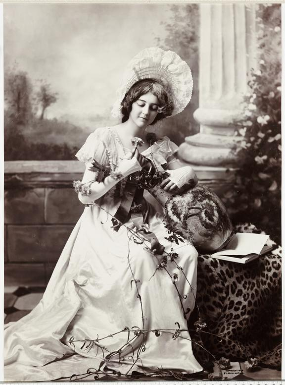 Woman taking flowers from a vase       A photograph of an elaborately dressed young woman admiring a flower, taken by James Arthur in 1899.