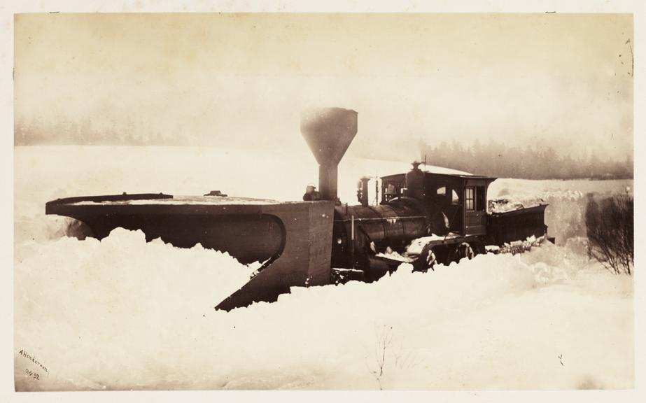 'Trains snowed up'       A photograph of a train fitted with a snowplough stuck in a snowdrift