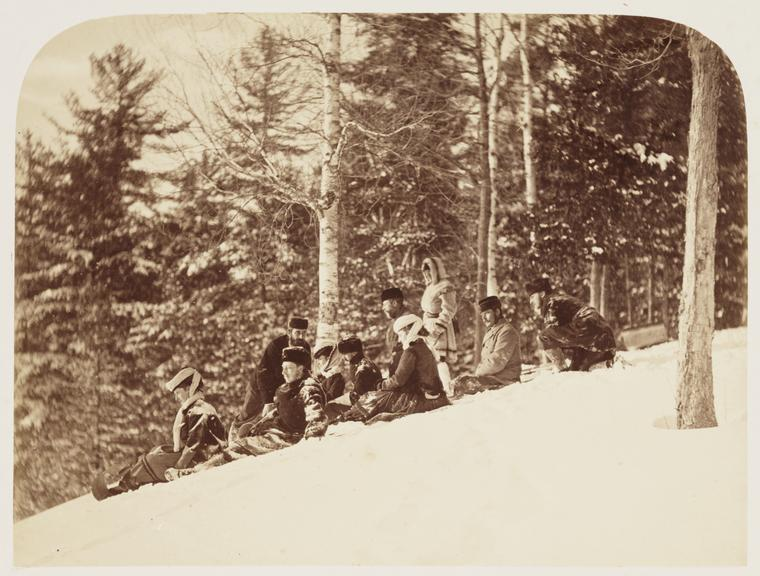 'Tobogganing'       A photograph of a group of men and women tobogganing down a snow-covered hill
