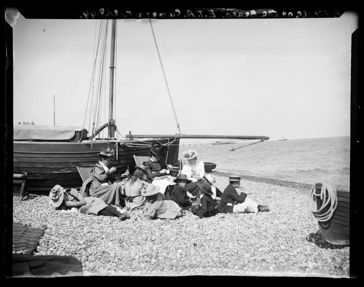 'A Picnic On The Beach', 1899       A photograph of a family, probably the Adams family, having a picnic on the beach at Deal, Kent