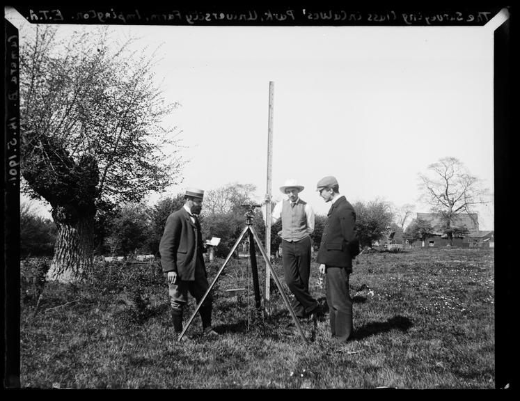 'The Surveying Class in Calves Park. University Farm Impington', 1901       A photograph of a land surveying class at University Farm, Impington, Cambridgeshire, with men using a theodolite