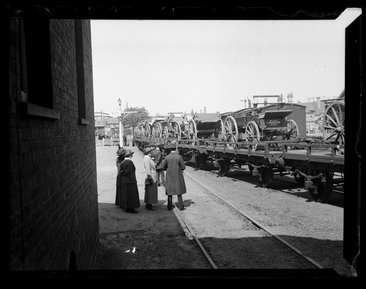 'Horse Drawn Vehicles Being Transported By Rail', about 1900       A photograph of horse drawn carriages being transported by rail on the back of wagons
