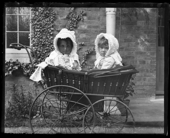 'Isobel And Pauline Adams In Pram', about 1890       A photograph of Isobel and Pauline Adams wearing matching bonnets and sitting in a pram, taken by their father
