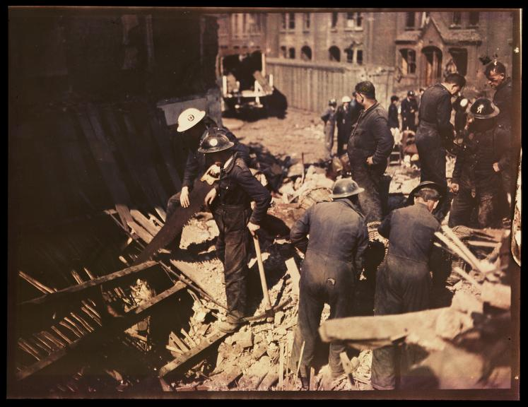 Clearing rubble       A Dufaycolor colour transparency of rescue workers at a bombed house in Britain