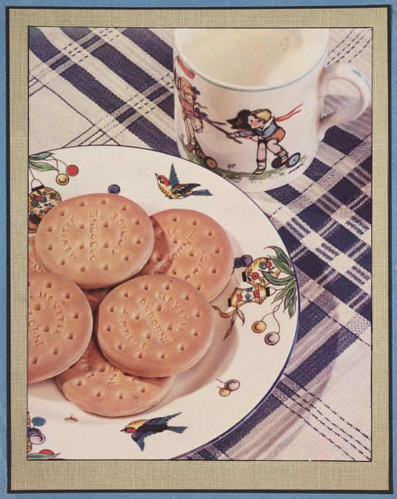 Milk and biscuits       A Vivex colour photograph of a cup of milk and a plate of biscuits, taken by an unknown photographer in about 1935