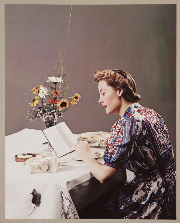 Woman reading a book       A Vivex colour photograph of a woman reading a book whilst eating a meal