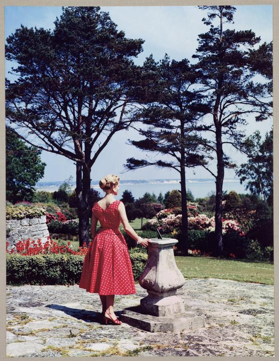 Woman standing by a sundial       A Dye Transfer colour photograph of a woman standing in a garden next to a sundial