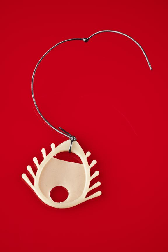 """Intra-uterine devices, """"Dalkon shield"""", plastic, 1 of 2, 1970-1981. Top View. Red Background"""