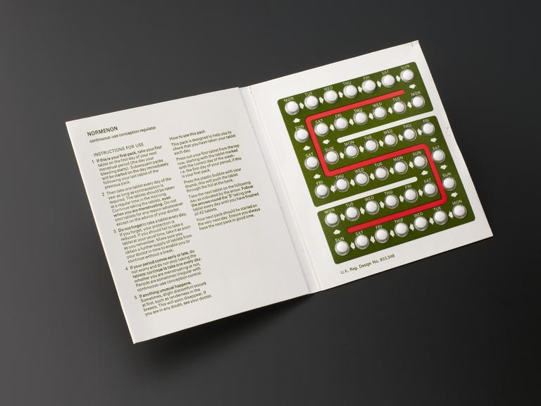 """Combined monophasic early contraceptive pills, """"normenon"""", packet, 1960-1970.  Front 3/4 view of whole object against"""