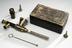 Endoscope (for aural, rectal or urethral use), in case.       Full view, instruments alongside case. Grey background.