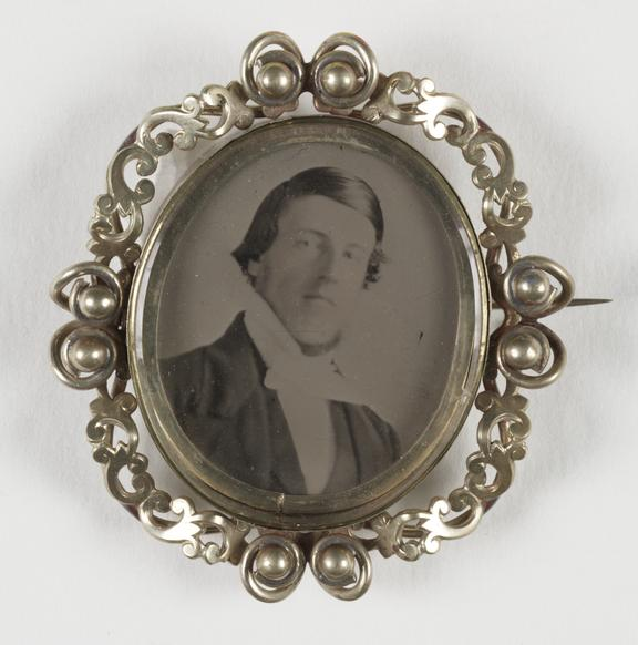 Brooch with ambrotype portrait of a man       A brooch containing a collodion positive photographic portrait of a young man